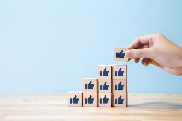 Koncepcje polubienia lub opinii z osobą tworzącą kciuki do góry znak na drewnianym stopniu