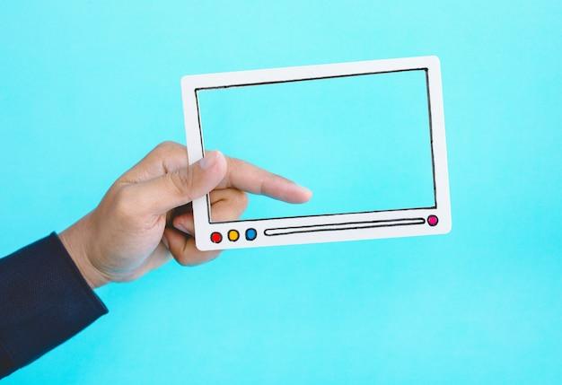 Koncepcje rozrywki społecznej i marketingu online męską ręką trzymającą kadr filmu wideo na niebieskim tle. pomysły na trendy cyfrowe
