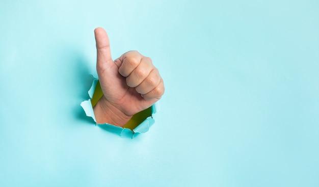 Koncepcje wyników efektu ręką pokazując kciuk w górę na niebieskim tle. kopia miejsca