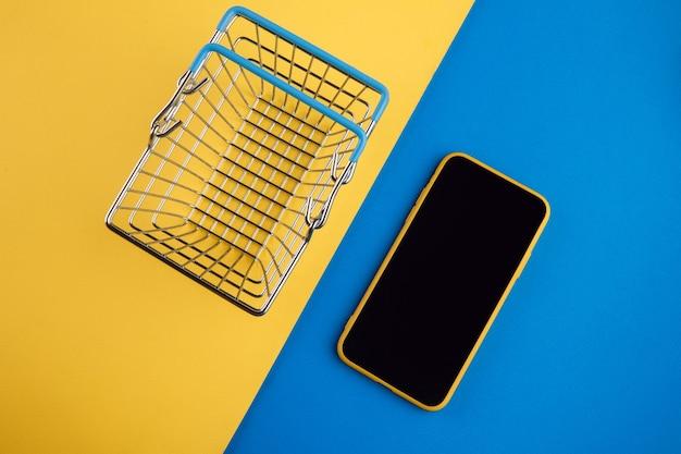 Koncepcje zakupów online z koszykiem i smartfonem na żółtym czerwonym tle. rynek e-commerce. logistyka transportu. handel detaliczny.
