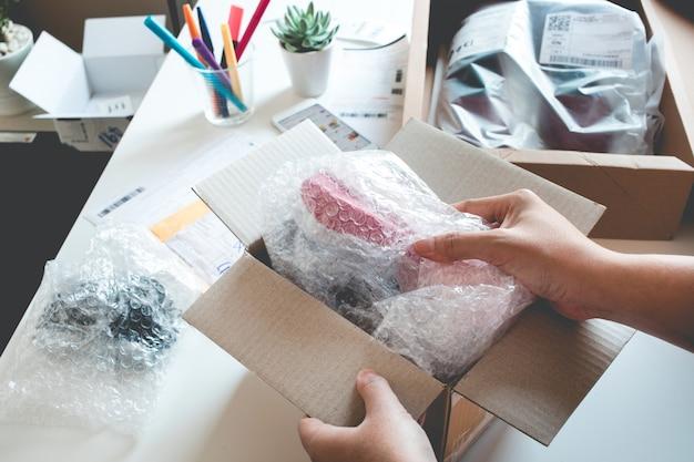 Koncepcje zakupów online z otwartym pudełkiem żeńskim, przedstawia produkt w dłoni