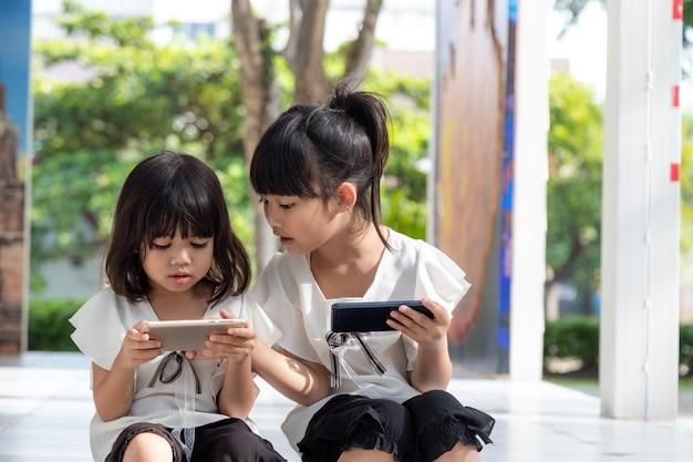 Koncepcyjne dzieci i gadżety dwie siostry rodzeństwa dziewczynek patrzą na telefon i uśmiechają się