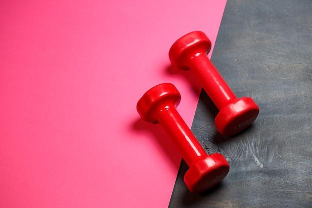 Koncepcyjne fitness i zdrowy sport tło z różowym hantle na różowym tle. widok z góry płasko świeckich z miejsca na kopię.