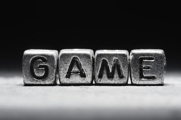 Koncepcyjne gra napis na metalowych kostkach na czarnym szarym tle z bliska na białym tle