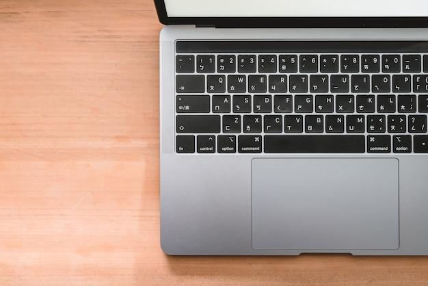 Koncepcyjne obszar roboczy, komputer przenośny z pustym białym ekranem na stole, niewyraźne tło. używać w systemie operacyjnym tradycyjnego alfabetu chińskiego.