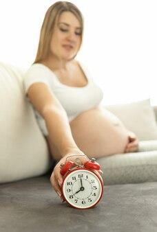 Koncepcyjne ujęcie kobiety w ciąży siedzącej na kanapie i trzymającej czerwony budzik