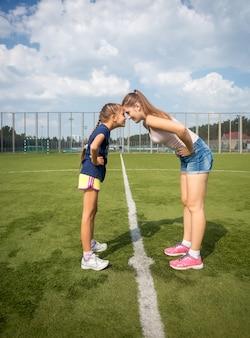 Koncepcyjne ujęcie plenerowe starszej i młodszej siostry stojącej łeb w łeb na trawie