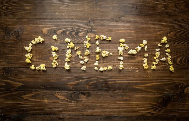 Koncepcyjne ujęcie słowa kino napisane przez popcorn i jądra na drewnianym tle