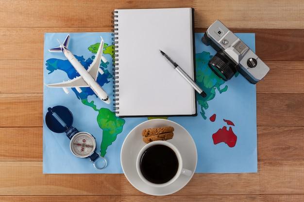 Koncepcyjne wakacje i turystyka z akcesoriami podróżnymi i filiżanką kawy