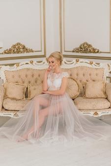 Koncepcyjne wesele, poranek panny młodej w europejskim stylu. sukienka buduarowa, opłaty we wnętrzu studio. biały minimalizm dla panny młodej