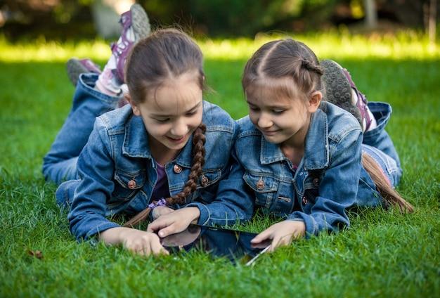 Koncepcyjne zdjęcie dwóch bliźniaczek korzystających z tabletu w parku