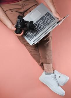 Koncepcyjne zdjęcie fotografa pracy. mężczyzna siedzi na różowo i trzyma laptopa i aparat