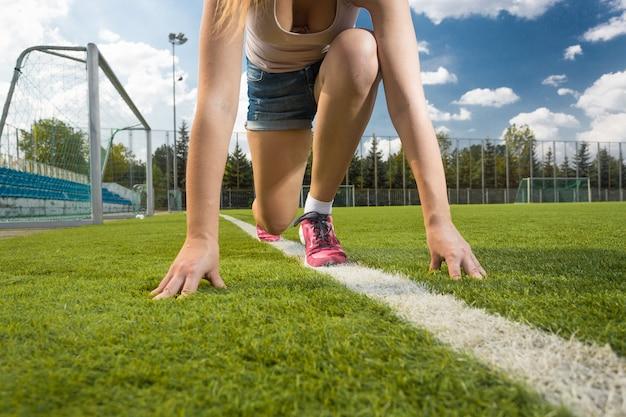 Koncepcyjne zdjęcie kobiety stojącej na pozycji startowej na polu trawy