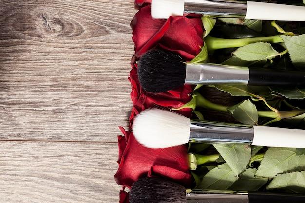 Koncepcyjny obraz pędzli do makijażu obok róż na drewnianym tle