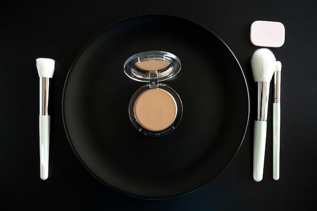 Koncepcyjny obraz pędzli do makijażu obok talerza obiadowego na czarnym tle
