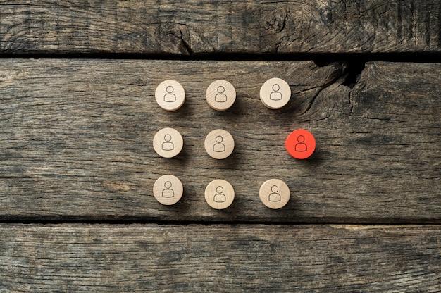 Koncepcyjny obraz wyjątkowości i indywidualności - czerwone drewniane wycięte koło z ikoną ludzi wyróżniające się z tłumu.