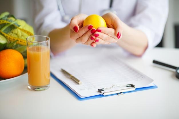 Konceptualna fotografia żeński nutritionist z owoc na biurku