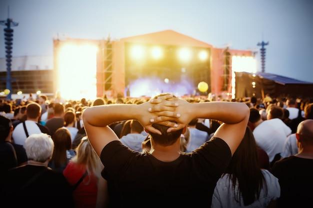 Koncert rockowy, wiwatujący tłum przed jasnymi, kolorowymi światłami sceny