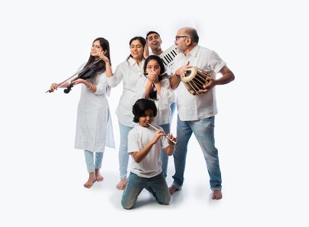 Koncert sześcioosobowej rodziny indyjskiej grającej na instrumentach muzycznych w grupie i śpiewającej starszej kobiety, stojącej na białym tle