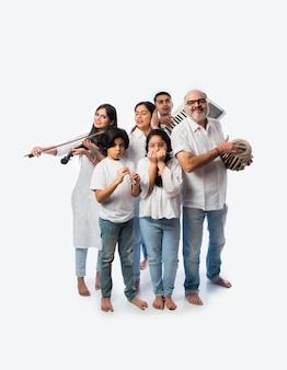 Koncert Sześcioosobowej Rodziny Indyjskiej Grającej Na Instrumentach Muzycznych W Grupie I śpiewającej Starszej Kobiety, Stojącej Na Białym Tle Premium Zdjęcia