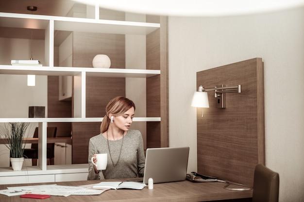 Końcowa praca. młoda atrakcyjna blondynka kończy pracę i popija herbatę