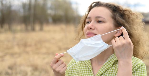 Kończąc izolację i kwarantannową koncepcję wirusa korony covid-19. 30-letnia młoda europejka usuwa z twarzy maskę medyczną i oddycha świeżym powietrzem na łonie natury
