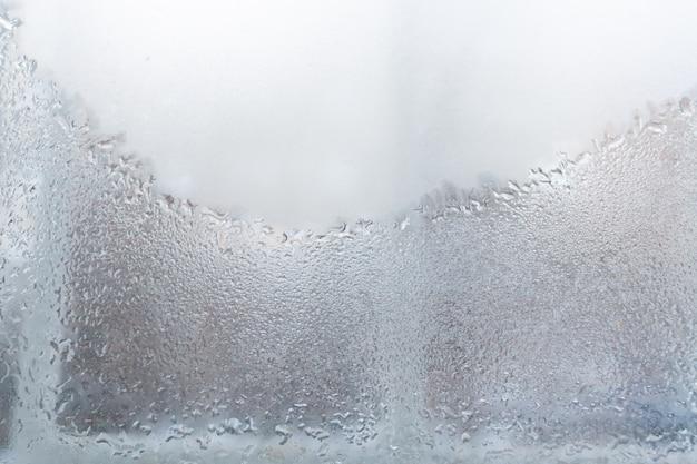 Kondensat z wody na spoconym, nieprzezroczystym szkle okiennym.