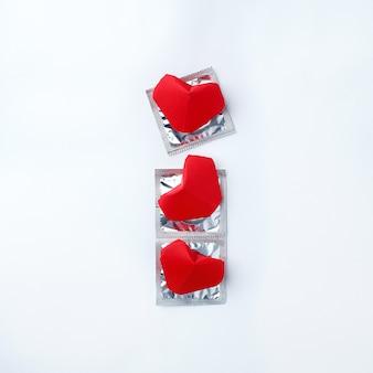 Kondomy i czerwoni serca na białym tle. koncepcja miłości. walentynki, wydarzenie romantyczne