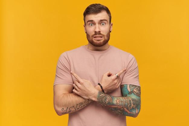 Konduowany przystojny wytatuowany młody brodaty mężczyzna w różowej koszulce, tworzący kształt litery x z rękami i wskazujący palcami po obu stronach na żółtej ścianie