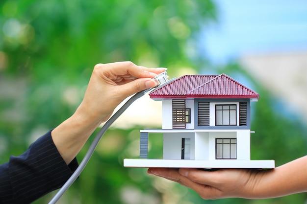 Kondycja finansowa, businesswoman za pomocą stetoskopu, aby sprawdzić model domu