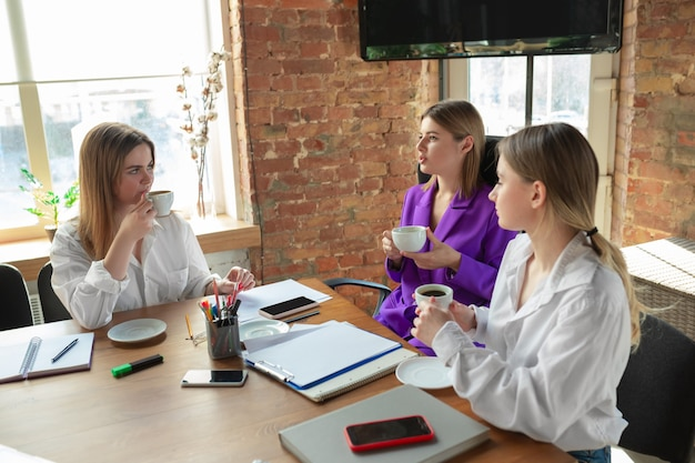 Konferencja. młoda biznesowa kaukaski kobieta w nowoczesnym biurze z zespołem. spotkanie, dawanie zadań. kobiety pracujące w biurze. pojęcie finansów, biznesu, girl power, integracji, różnorodności, feminizmu.