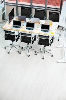 Konferencyjna sala konferencyjna stół roboczy w biurze firmy pełnym laptopów notebooki czarne filiżanki gorącej kawy i dane z raportów dokumenty dokumenty i czarne krzesła z miejscem na kopię na drewnianej podłodze.