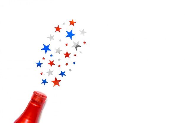 Konfetti gwiazd w kolorze amerykańskiej flagi wylatują z butelki na białym tle. miejsce na tekst. czwarty lipca. wystrój na dzień niepodległości ameryki.
