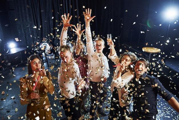 Konfetti jest w powietrzu. grupa wesołych przyjaciół z okazji nowego roku w pomieszczeniu z napojami w rękach.