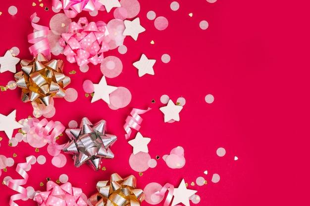 Konfetti, kokardki i papierowe dekoracje. motyw koncepcyjny walentynki lub przyjęcie urodzinowe. płaski układanie, widok z góry