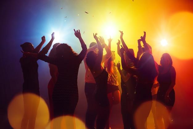 Konfetti. tłum ludzi w sylwetce podnosi ręce na parkiecie na neonowym tle. życie nocne, klub, muzyka, taniec, ruch, młodzież. żółto-niebieskie kolory i poruszające dziewczyny i chłopcy.