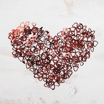 Konfetti tworząc serce z białym drewnianym tłem