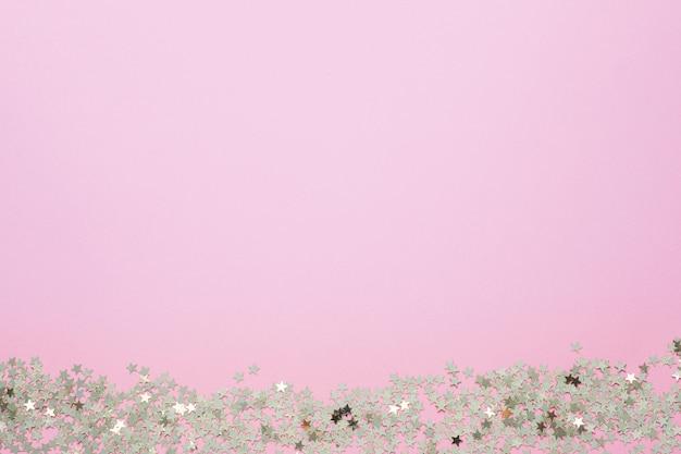 Konfetti złotych gwiazd błyszczą na różowym tle. świąteczne wakacje