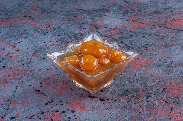 Konfitura figowa w szklanym kubku na niebieskim tle.