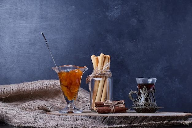 Konfitura, paluszki waflowe i szklanka herbaty.
