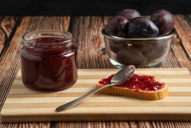 Konfitura śliwkowa w szklanym słoiku z pieczywem tostowym i owocami.