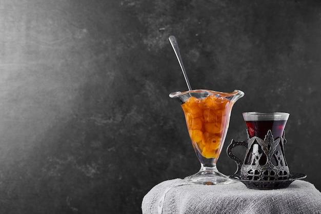 Konfitura wiśniowa podawana ze szklanką herbaty.
