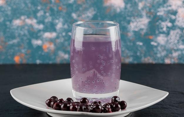 Konfitura z czarnej porzeczki na białym spodku, dookoła szklanka soku.