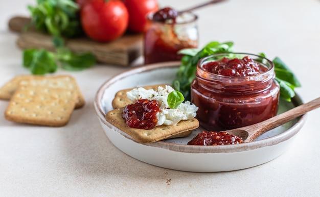 Konfitura z konfitur lub sos z pomidorów z krakersami i sałatką z zielonych liści niezwykła konfitura na słono