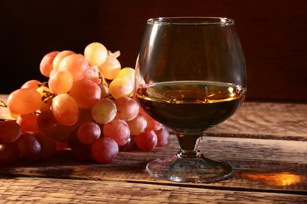 Koniak lub brandy w szklance i świeżych winogronach, martwa natura w stylu rustykalnym