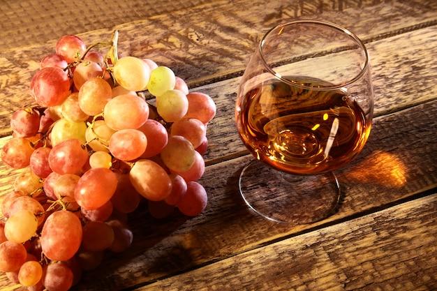 Koniak lub brandy w szklanych i świeżych winogronach życie w wieśniaka stylu wciąż, rocznika drewniany, selekcyjny ostrość.