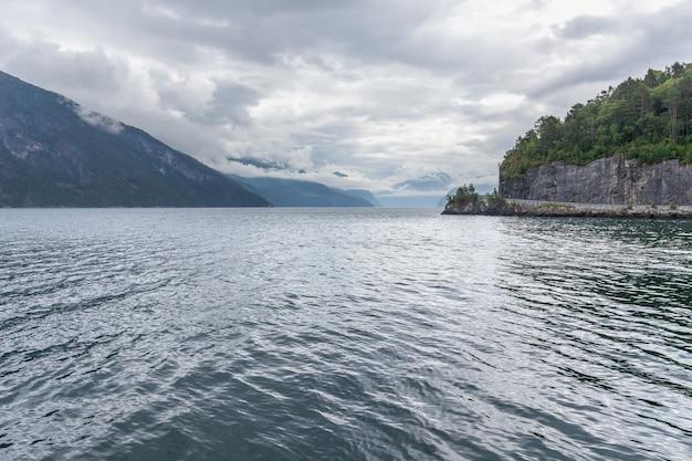 Koniec fiordu. piękny norweski krajobraz. widok na fiordy. norwegia idealne odbicie fiordu w czystej wodzie przy pochmurnej pogodzie.