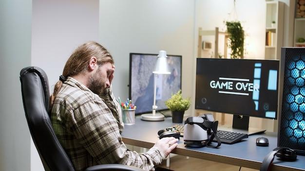 Koniec gry dla człowieka siedzącego na fotelu do gier za pomocą zestawu słuchawkowego vr. nowoczesna technologia do gier.