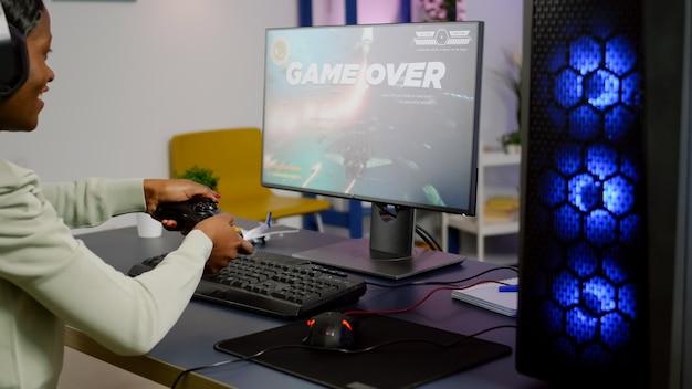 Koniec gry dla streamera grającego w gry wideo typu space shooter w domu za pomocą profesjonalnego kontrolera bezprzewodowego