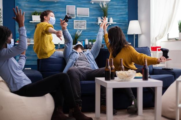 Koniec gry dla wielokulturowych przyjaciół podczas grania w gry wideo za pomocą joysticka, zachowując dystans społeczny z maską na twarz z powodu epidemii koronawirusa na świecie siedząc na kanapie.